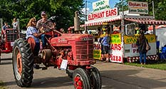 Photo: Red tractor in parade at the Wayne County Fairgrounds, in front of food stand.