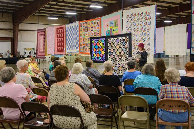Ladies sitting in chairs in front of a row of quilts. Copyright: HolmanPhotos.com