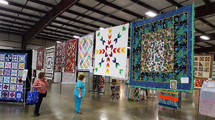 Supplied Photo: Quilts hanging in the Tom Raper Center with two women looking at them.